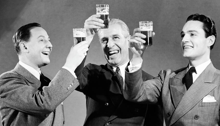 three-men-making-toast-with-glasses-of-beer-bw-hulton-archive